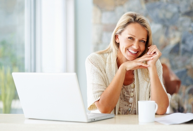 Cheerful Woman With Laptop And Tea Cup - Copy Space